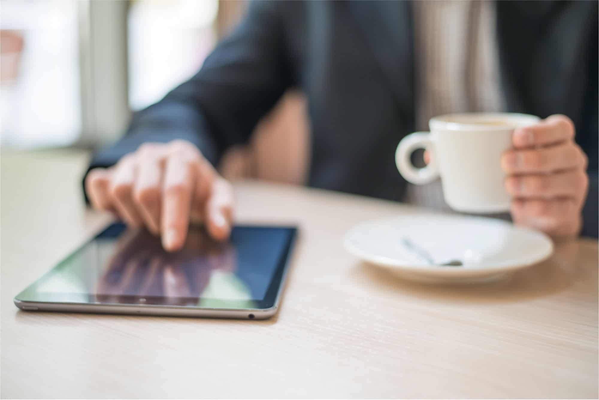 Mann liest Nachrichten auf dem Tablet